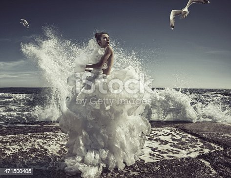 women in plastic bag dress at sea wave background