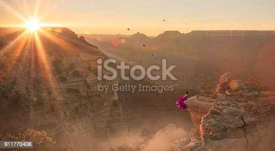 istock Women in purple dress sitting at edge of Grand Canyon 911770406