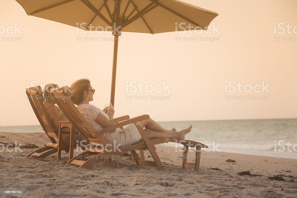 women in recliners enjoying a glass of wine and sunset stock photo
