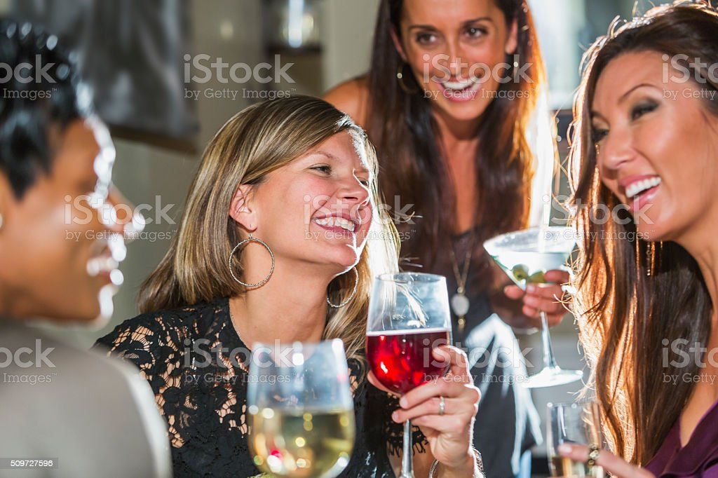 Women in restaurant with friends drinking and laughing stock photo