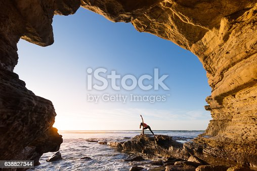 Dreamy warm sun light with a Women In Salutation Pose In An Ocean Cave