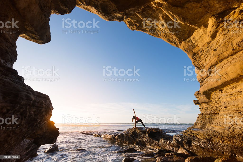 Women In Salutation Pose In An Ocean Cave stock photo