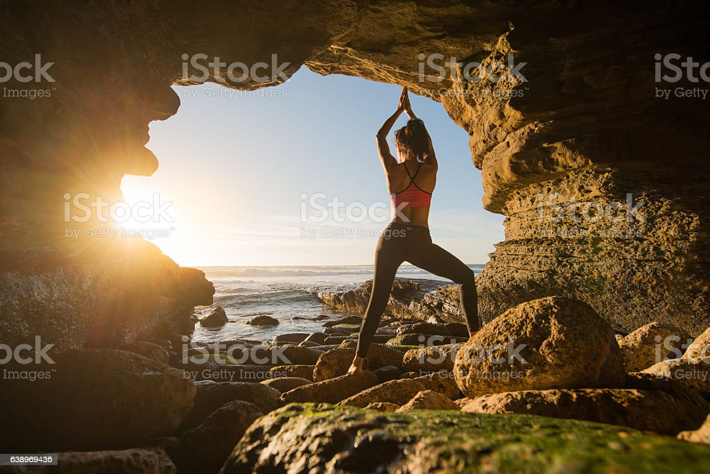 Women In Salutation Pose In An Ocean Cave - Photo