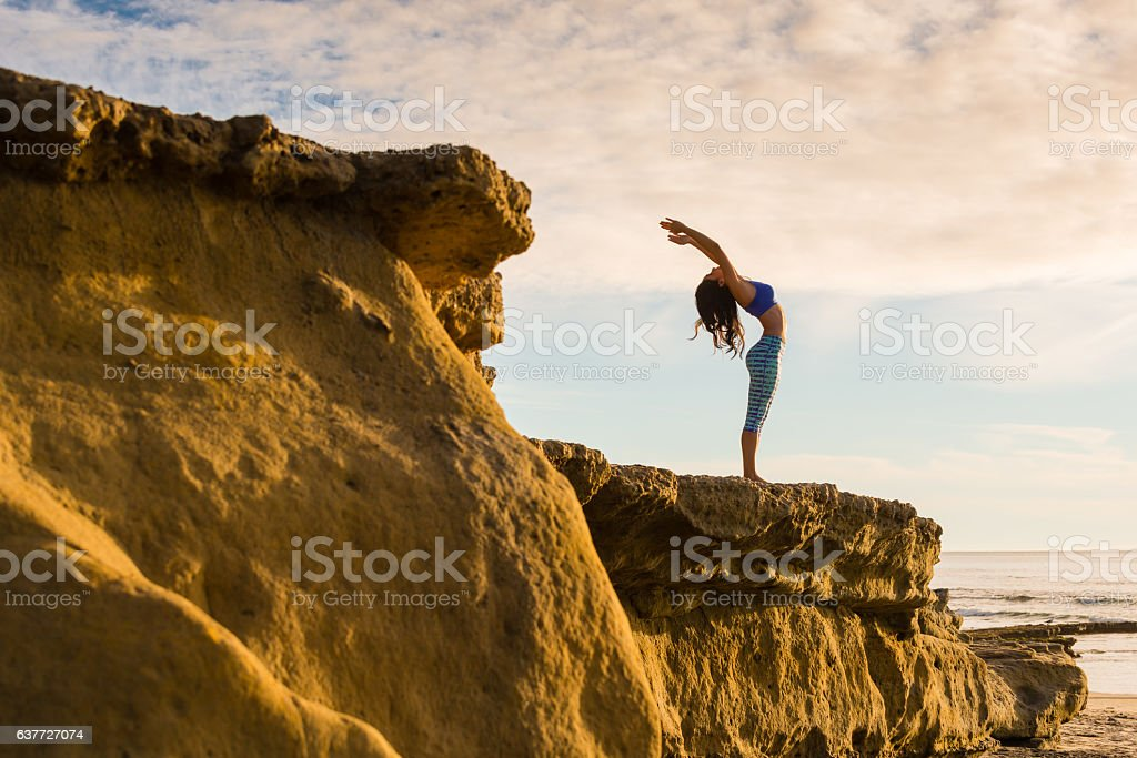 Women In Salutation Pose On A Bluff At The Ocean stock photo