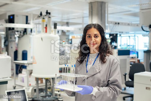 A mixed race female scientist stands in her laboratory, she is holding body fluid samples and is wearing protective workwear. In the background there is a vast array of specialist research equipment, she is about to run some human medical samples. New forms of innovation are being trialed, with investment in new technologies.