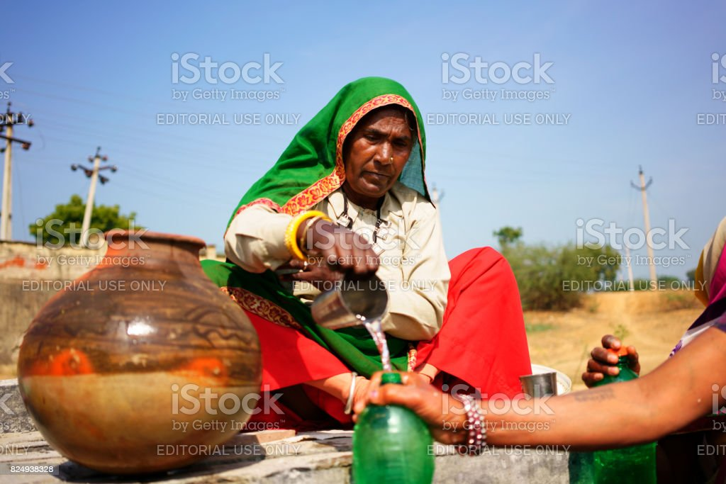 women in solidarity act provides water to another stock photo