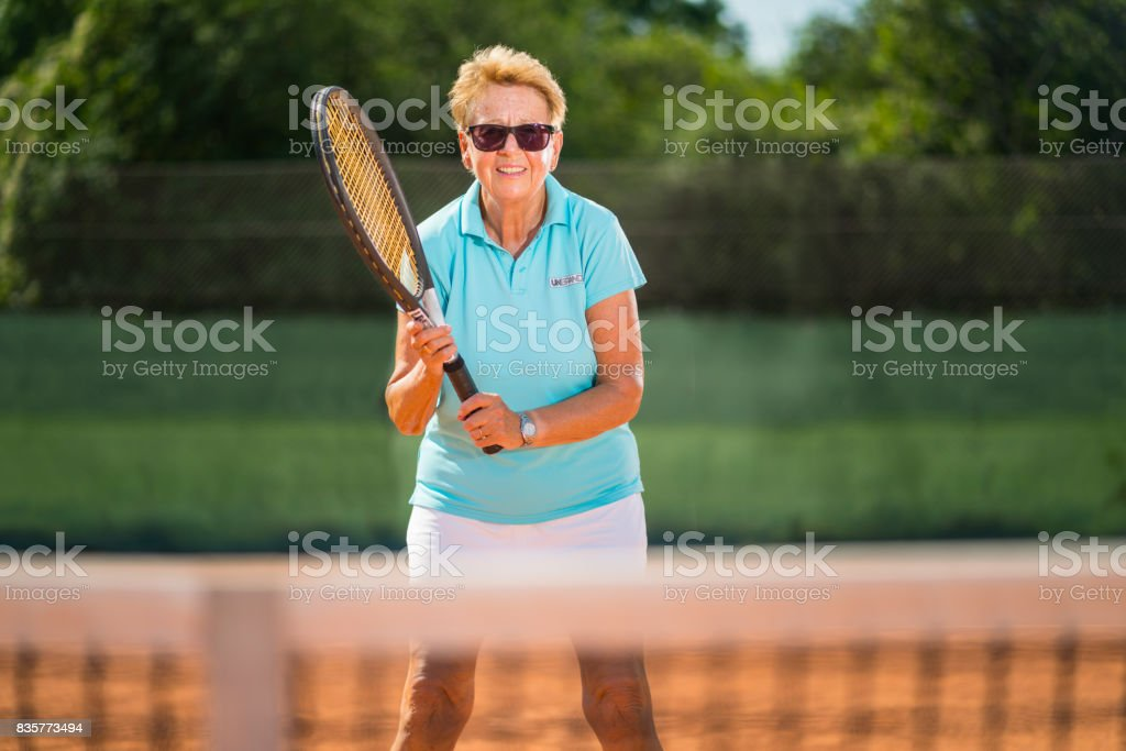 Women in Sport, 70 years old female tennis player waiting at net stock photo