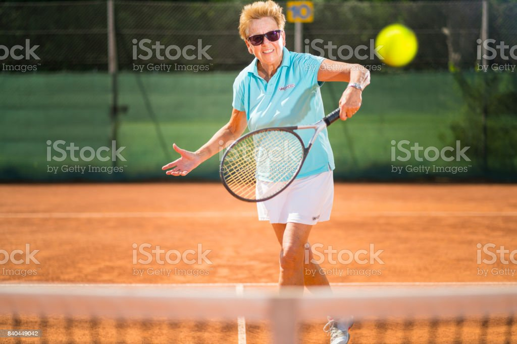 Women in Sport, fit senior woman playing tennis on clay court stock photo