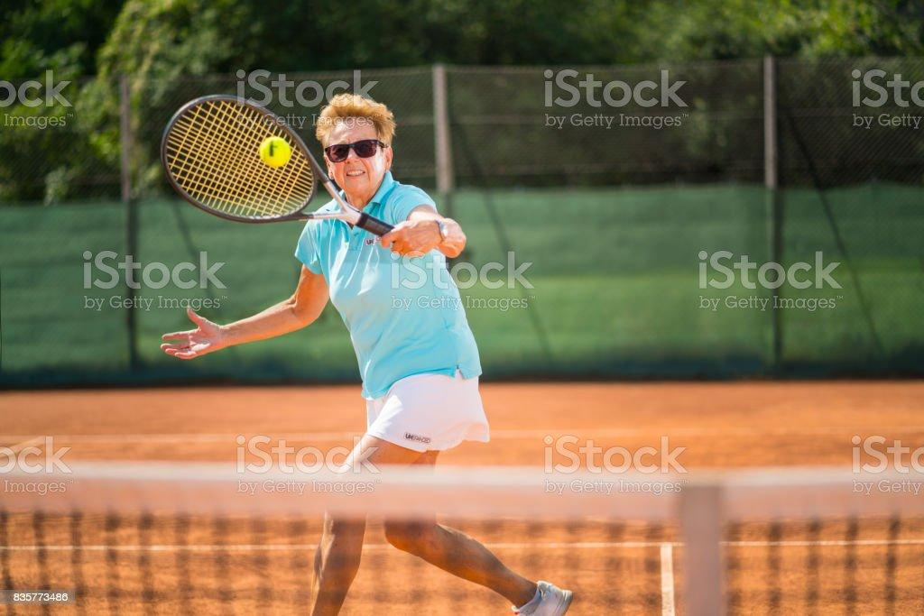 Women in Sport, fit senior woman playing tennis stock photo