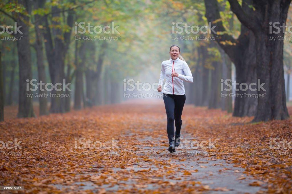 Women in Sport - running training in alley in autumn stock photo