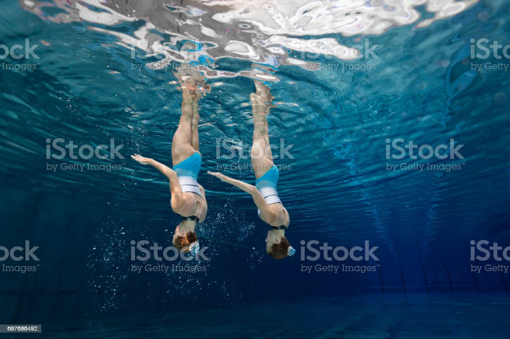 Women in Sport, teenage girls underwater synchronized swimming stock photo