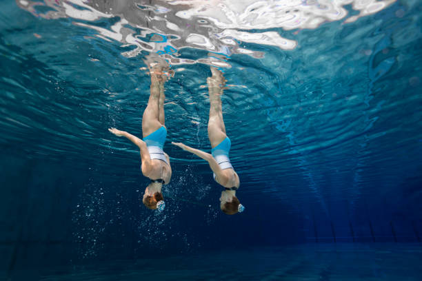 women in sport, teenage girls underwater synchronized swimming - symmetry stock photos and pictures