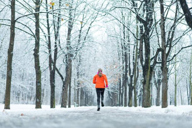 kvinnor i sport - kvinna kör i vintern gränd med snö bakifrån - winter austria train bildbanksfoton och bilder