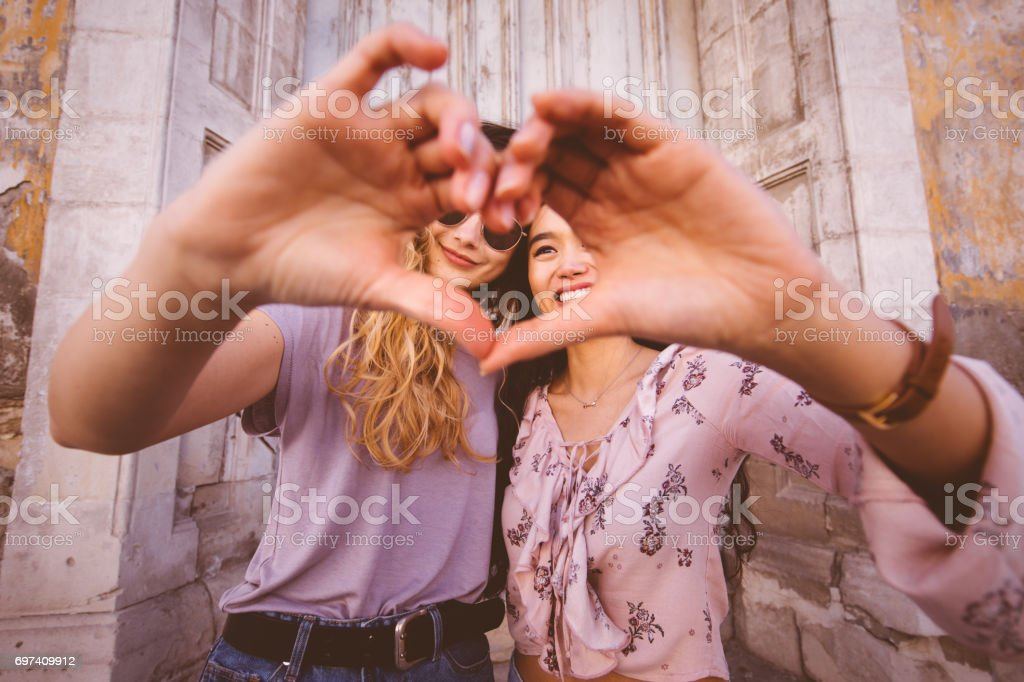 Women in the city making heart shape with their hands stock photo