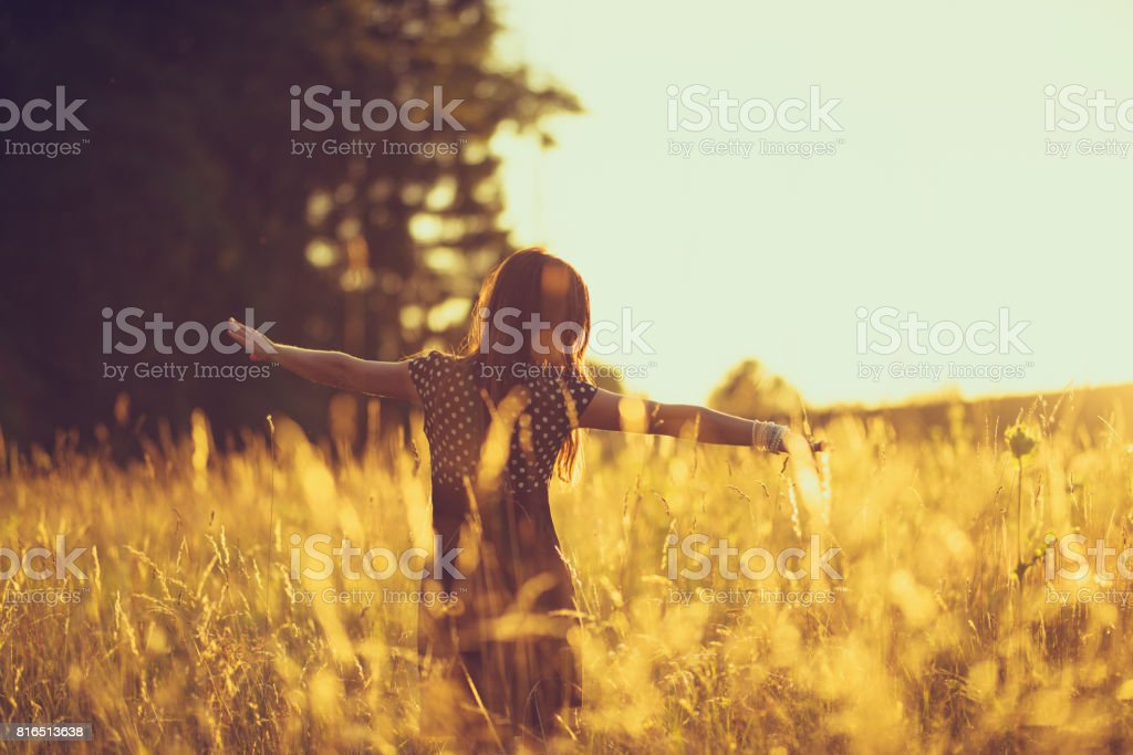 women in the evening sky in a meadow stock photo