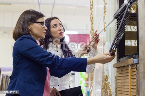 Women in the store choose blinds for windows