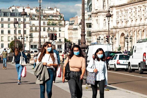 femmes dans la rue, portant un masque de protection pour prévenir le coronavirus. - covid france photos et images de collection