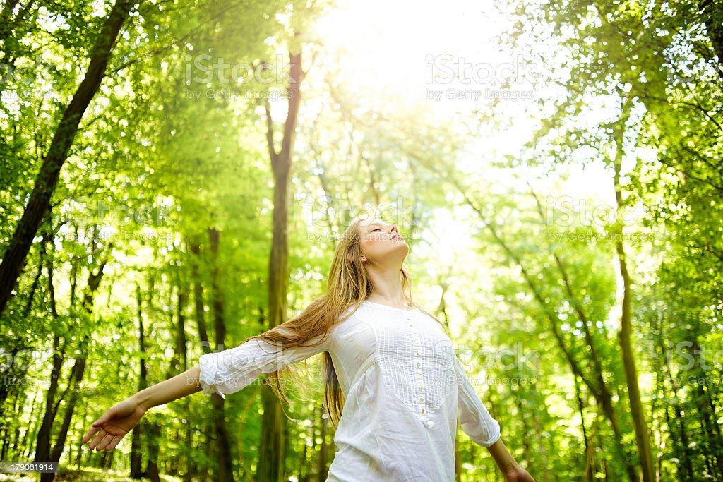 A women in the woods basking in the sun stock photo