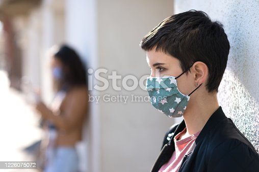 Women in town wearing protective masks and gloves during COVID-19 pandemic.
