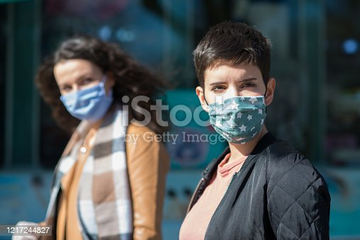 Women In Town Wearing Protective Face Masks and protective gloves during COVID-19 pandemic.