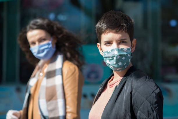 Women In Town Wearing Protective Face Masks and protective gloves stock photo
