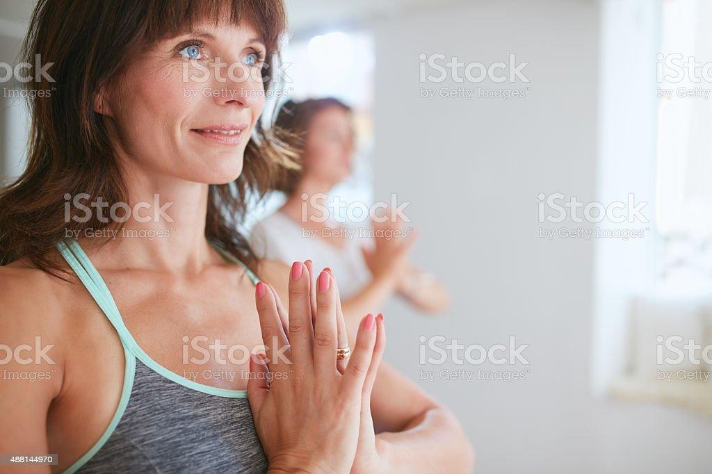 Women in tree pose yoga with Namaste stock photo