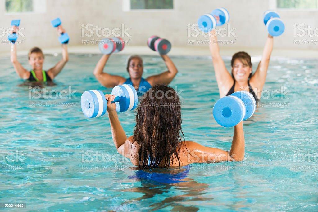 Donna in acqua aerobica esercizi in classe con istruttore - foto stock