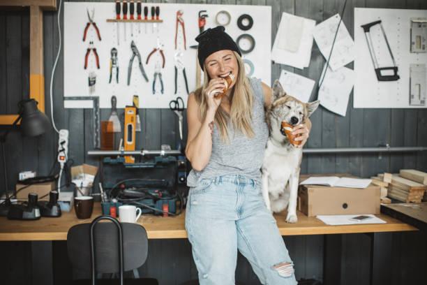 frauen in der werkstatt mit ihrem haustier hund - essen tattoos stock-fotos und bilder