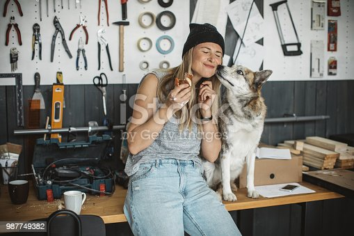 Woman manual worker have a breakfast, her pet dog is come to say hello. She is in workshop and all different types of tools are around her.