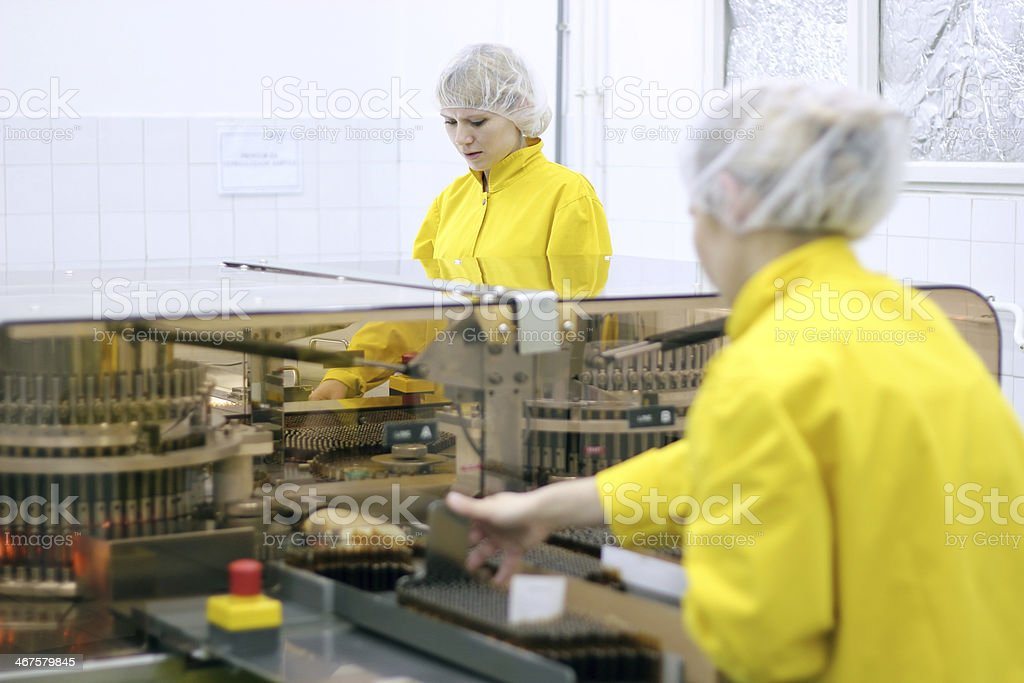 Women in yellow hygienic wear inside a pharmaceutical lab stock photo