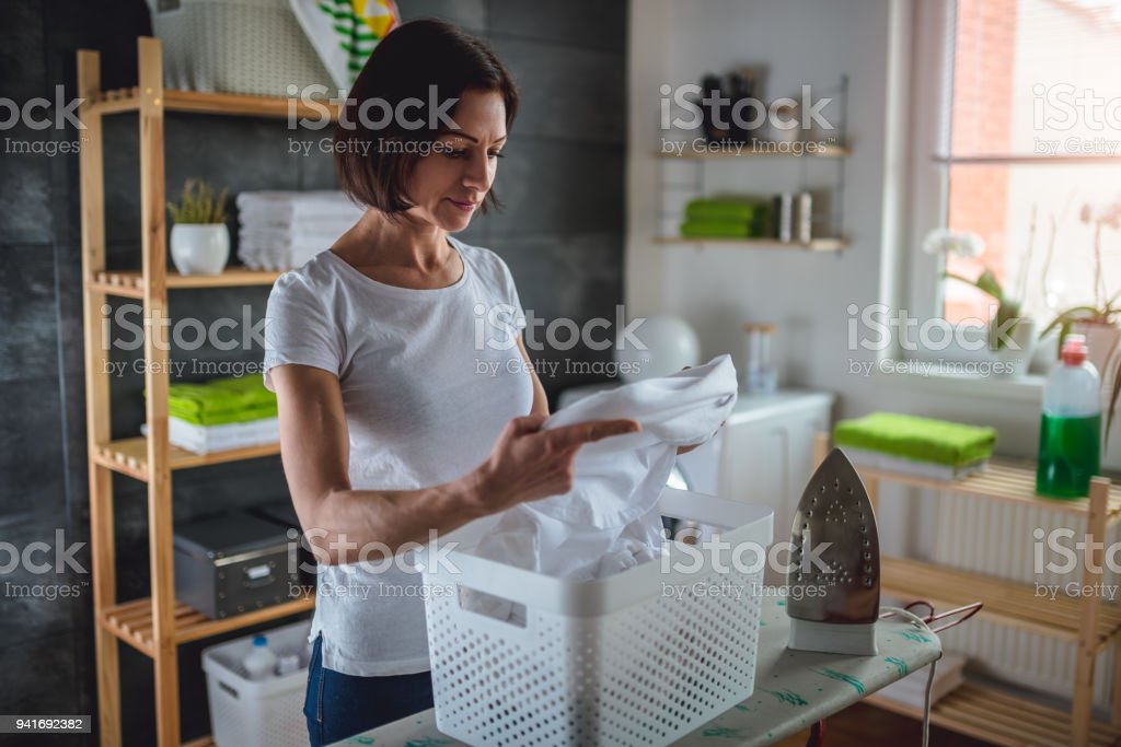 Women inspecting clothes in basket at laundry room stock photo