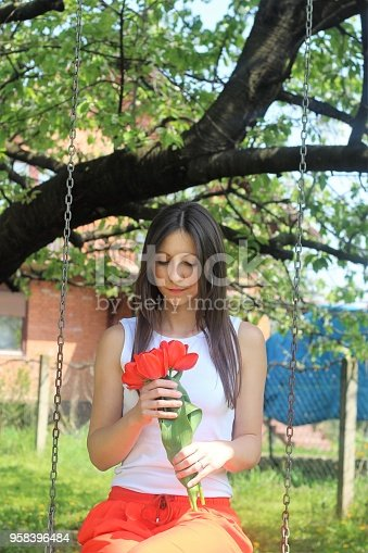 Women and red tulips on swing.