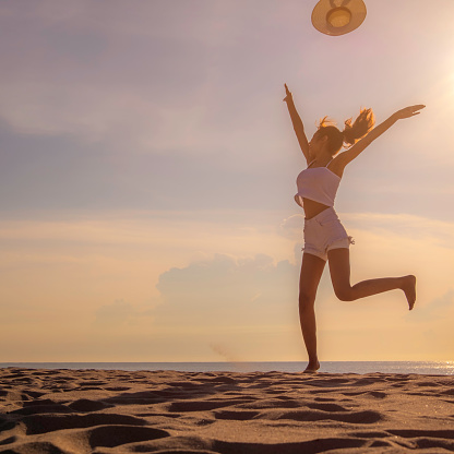 Women Jump On The Beach With Happy Acting During Sunset With Silhouette Picture That Filling Freedom Stock Photo - Download Image Now