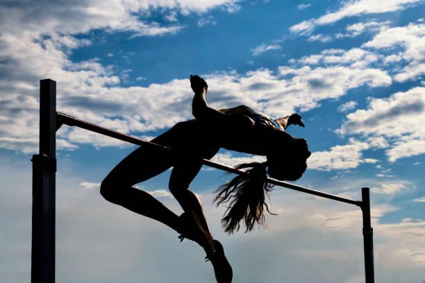 Frauen, die einen Sprung über die Leiste, Silhouette – Foto