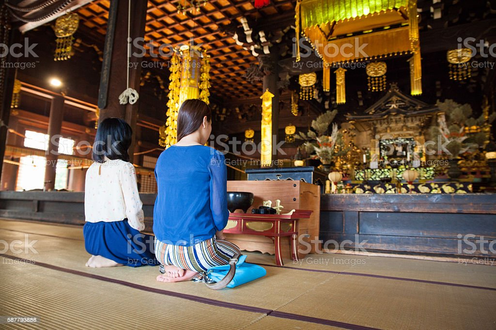 Women kneeling and praying in a buddhist temple - foto de acervo