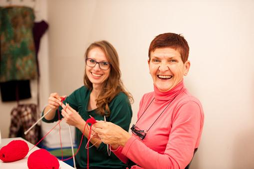Women knitting with red wool. Eldery woman transfering knitting knowledge