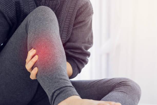 女性は朝、ベッドの上で痛みを遅らします。 - 脛 ストックフォトと画像