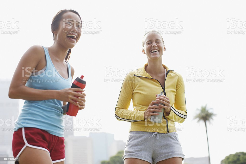 Women laughing and holding water bottles stock photo