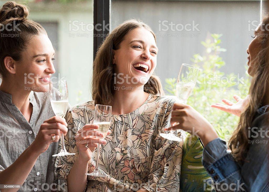 Mulheres rindo no bar com taças de vinho - foto de acervo