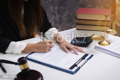 1070981872istockphoto Women lawyer working with contract papers and wooden gavel on table in courtroom. justice and law ,attorney, court judge, concep 1068791052