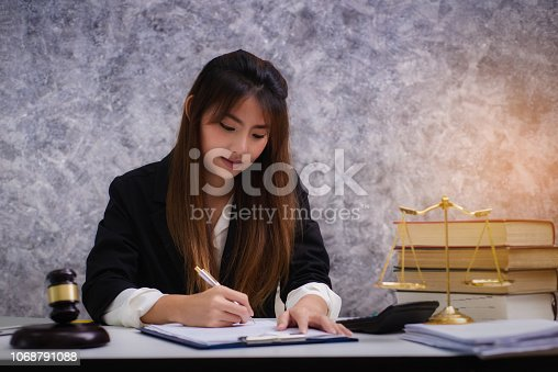 1070981872istockphoto Women lawyer working with contract papers and wooden gavel on table in courtroom. justice and law ,attorney, court judge, concep 1068791088