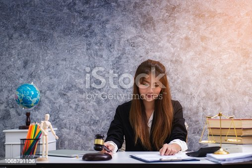 1070981872istockphoto Women lawyer working with contract papers and wooden gavel on table in courtroom. justice and law ,attorney, court judge, concep 1068791136
