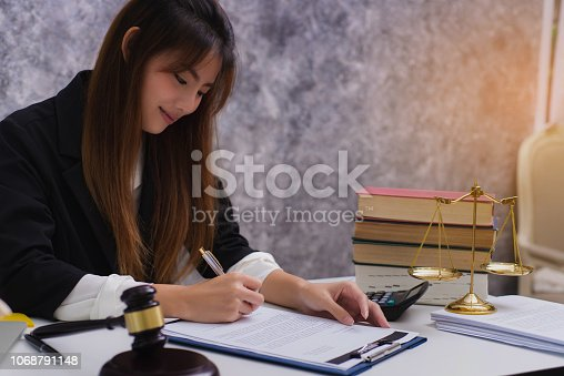 1070981872istockphoto Women lawyer working with contract papers and wooden gavel on table in courtroom. justice and law ,attorney, court judge, concep 1068791148