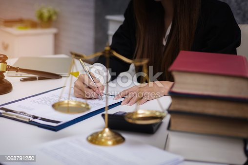 1070981872istockphoto Women lawyer working with contract papers and wooden gavel on table in courtroom. justice and law ,attorney, court judge, concep 1068791250