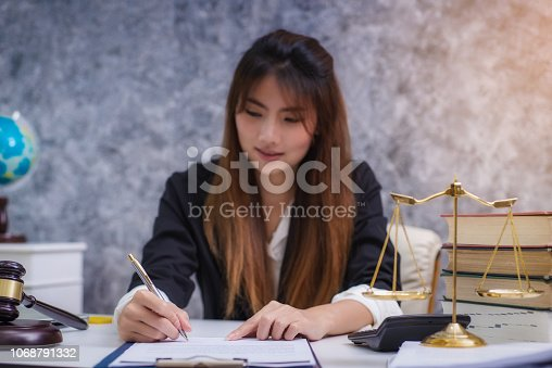 1070981872istockphoto Women lawyer working with contract papers and wooden gavel on table in courtroom. justice and law ,attorney, court judge, concept. 1068791332