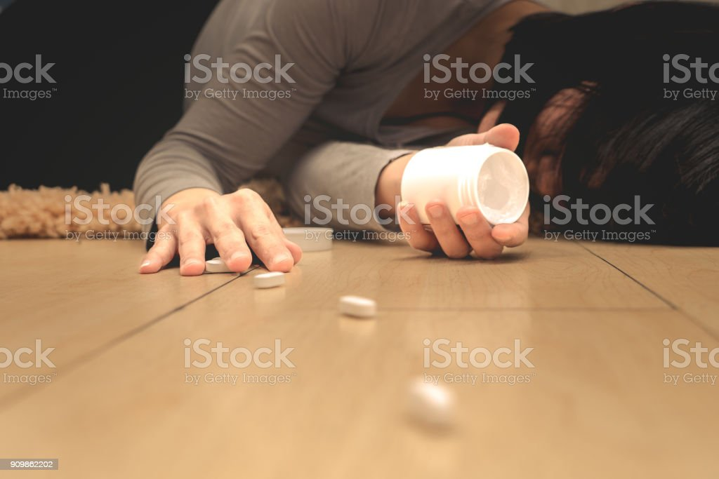 women lay down after taking medicine overdose with open pills bottle. Concept of overdose and suicide. stock photo
