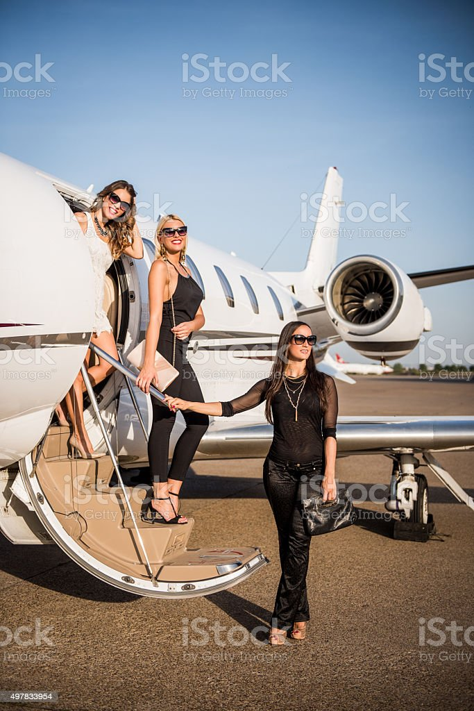 Women leaving the private jet airplane stock photo