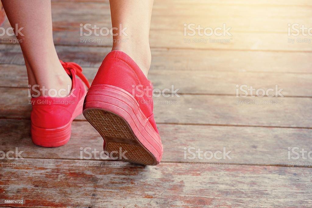 women legs wearing red shoes walking on wooden floor stock photo