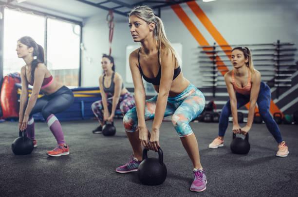 Mujeres levantamiento kettlebells en el gimnasio. - foto de stock