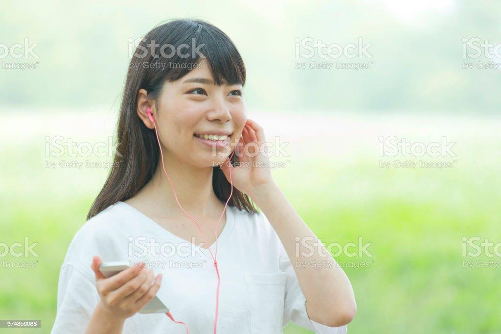 女性が新鮮な緑色でイヤホンで音楽を聞く ストックフォト